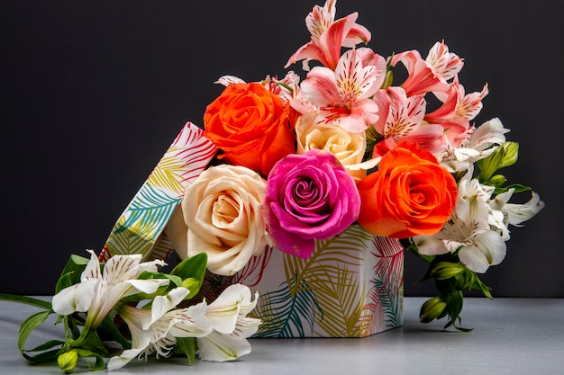Вид сбоку букета из разноцветных роз и альстромерии розового цвета в подарочной коробке на черном столе