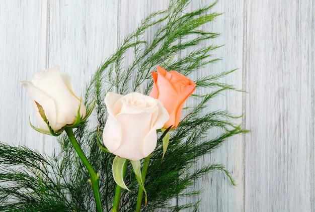 회색 나무 배경에 아스파라거스와 복숭아와 크림 색 장미 꽃다발의 측면보기