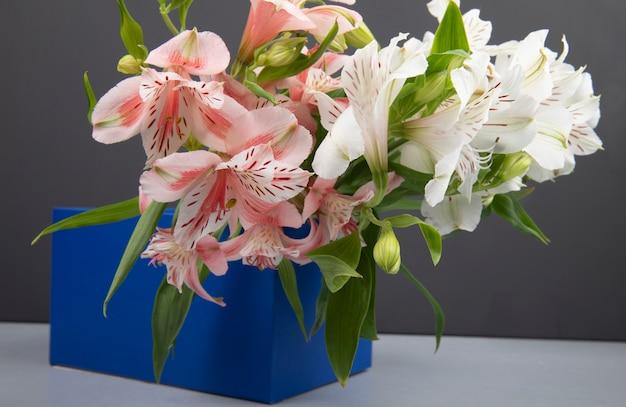 Вид сбоку на букет цветов альстромерии розового и белого цвета в синей коробке на сером фоне
