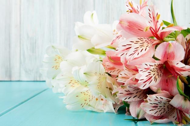 青い木製の背景にピンクと白の色のアルストロメリアの花の花束の側面図