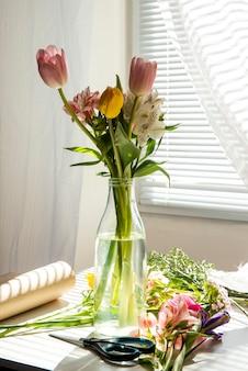 Вид сбоку букета розовых и желтых цветных тюльпанов с цветами альстромерии в стеклянной бутылке на столе
