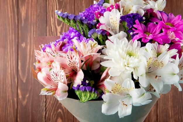 Вид сбоку букет из розовых белых и фиолетовых цветов статицы альстромерии и хризантемы в крафт-бумаге, изолированных на деревенском фоне