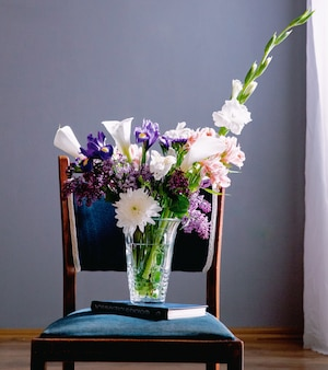 Вид сбоку букета калл лилий белого цвета с темно-фиолетовым ирисом сирени и белых гладиолусов в стеклянной вазе, стоящей на книге на стуле на сером фоне стены