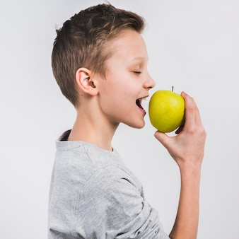 白い背景に分離された緑の新鮮なリンゴを食べる少年の側面図