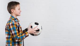 手に白いレンガの壁に立っているサッカーを持つ男の子の側面図