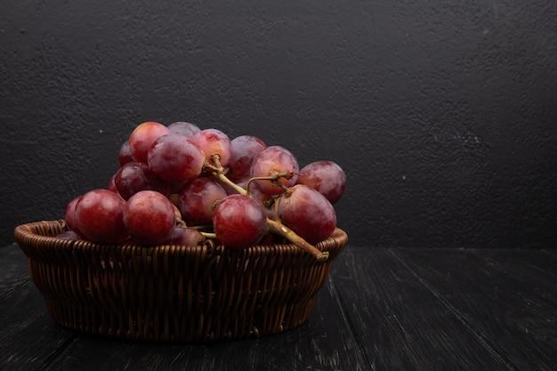 暗い木製のテーブルに籐のかごで新鮮な甘いブドウの房の側面図
