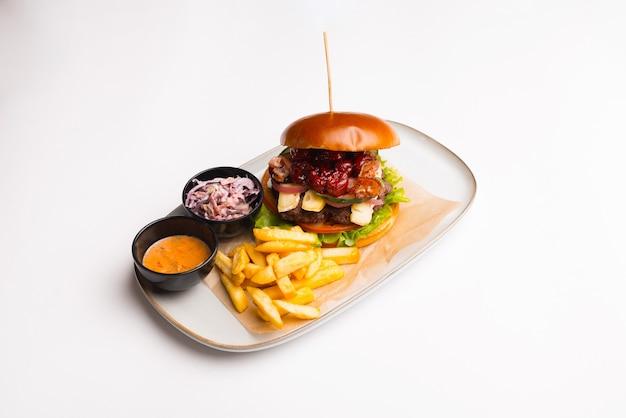Вид сбоку гамбургера на белой тарелке с картофелем фри.