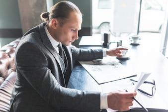カフェで文書をチェックしているビジネスマンの側面図