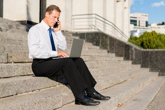 Side view of a businessman talking on mobile phone while using laptop