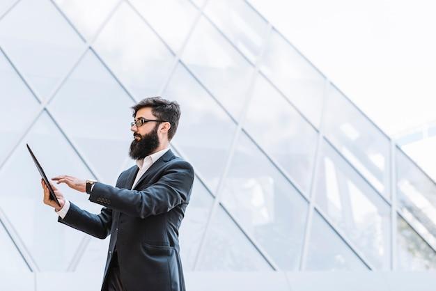 Вид сбоку бизнесмена с длинной бородой, используя цифровую табличку, стоящую против стеклянного здания