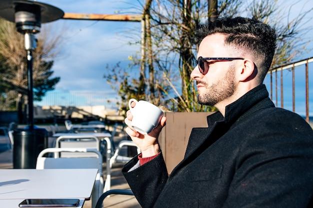 Вид сбоку бизнесмена с подстриженной бородой и солнцезащитными очками за чашкой кофе на террасе бара.