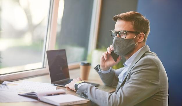 노트북을 사용하여 보호용 안면 마스크를 쓰고 전화로 이야기하는 바쁜 사업가의 측면