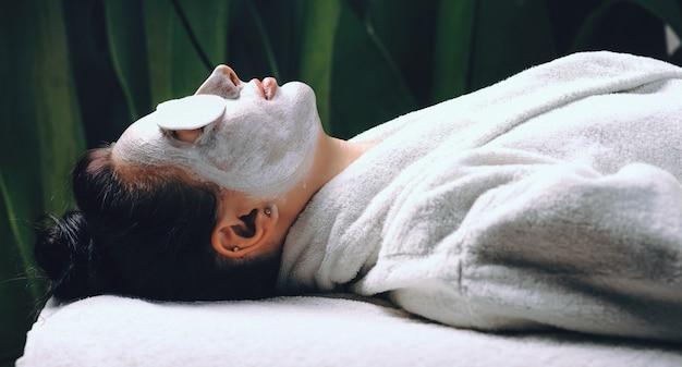 Вид сбоку кавказской дамы, лежащей в спа-салоне с белой маской на лице и некоторыми дисками на глазах