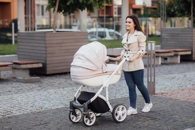 乳母車に座っている彼女の幼児を押しながら街の通りを歩いている白人の母の側面図
