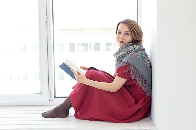 긴 수수한 드레스와 스카프를 입은 매력적인 어린 소녀의 옆모습은 창턱에 앉아 책을 읽고 있습니다. 젊음과 낭만주의의 개념.