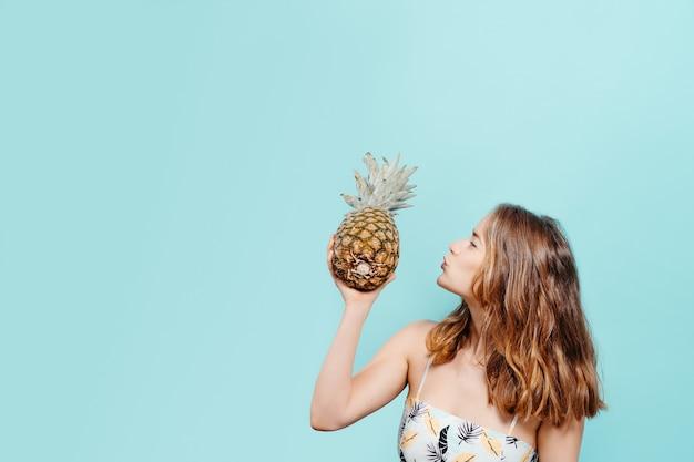 Вид сбоку веселой молодой блондинки, держащей ананас с милым поцелуем в летнем топе на синем фоне