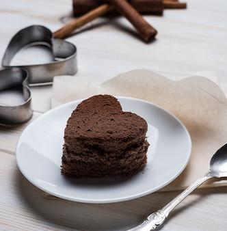 실버 스푼과 철제 형태와 계피 스틱 옆에 접시에 누워 심장 모양의 초콜릿 디저트 비스킷의 측면보기