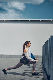 彼女の左足を伸ばしている流行のスニーカーで集中したスポーティな若い女性の側面図