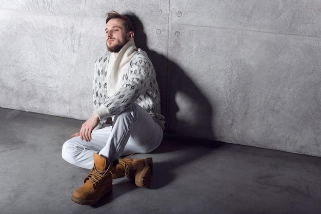 Вид сбоку уверенного в себе бородатого молодого человека в белых джинсах и кардигане, сидящего