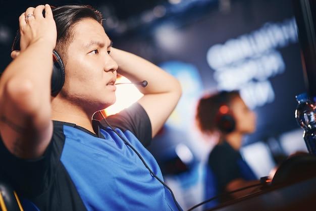 Eスポーツトーナメントに参加し、オンラインビデオゲームをプレイしながら、混乱したアジア人の男の側面図、悲しい表情でpc画面を見ているヘッドフォンを身に着けている男性のサイバースポーツゲーマー