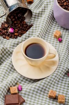 Вид сбоку чашки кофе и коричневого сахара кубиками шоколада и кофейных зерен, разбросанных на клетчатой скатерти