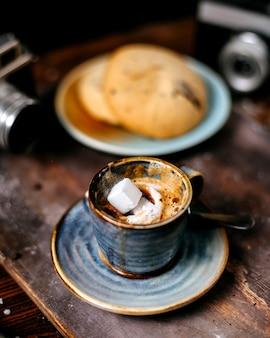 Вид сбоку чашку кофе эспрессо с печеньем на деревенском backgraund