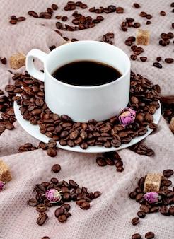 Вид сбоку чашки кофе с кофейными зернами и кубиками коричневого сахара Бесплатные Фотографии