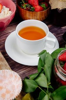 Вид сбоку чашку чая со свежей спелой клубники на деревенском