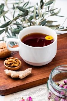 Вид сбоку чашку чая с имбирем и грецкими орехами на деревянной доске