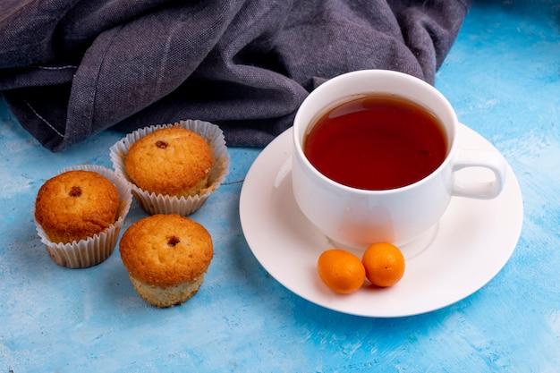 Вид сбоку чашку чая с вкусной булочки на синем столе