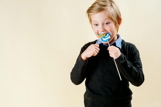口を大きく開けて夜用セーターを着たかわいい子供の側面図は、明るい背景に青いロリポップを食べます。小さな男の子は、スタジオで分離されたおいしい砂糖ロリポップを舐めています。