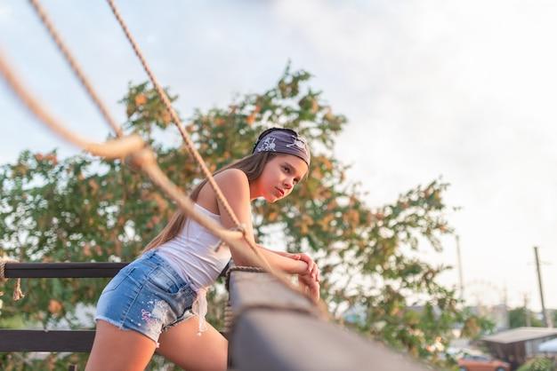 ショートパンツと帽子のかわいいティーンエイジャーの女の子の側面図は、オープンバルコニーに立っています