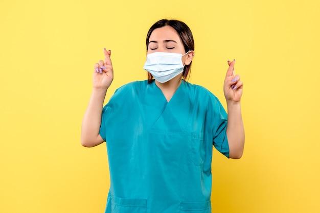 마스크에있는 의사의 측면보기 마스크에있는 의사는 covid가있는 모든 환자의 회복을 희망합니다.