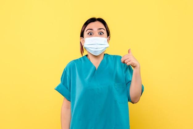 마스크를 쓴 의사의 측면에서 코로나 바이러스의 증상에 대해 이야기하고 있습니다.