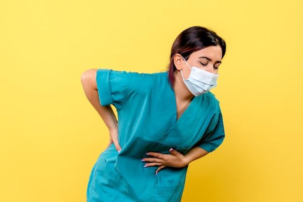 마스크를 쓴 의사의 측면이 코로나 바이러스의 증상에 대해 이야기하고 있습니다.
