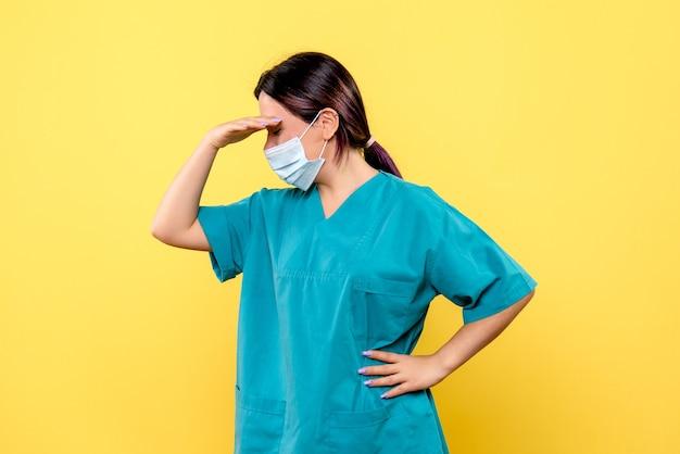 마스크를 쓴 의사의 측면 모습은 코 비드 환자에 대해 생각하고 있습니다.