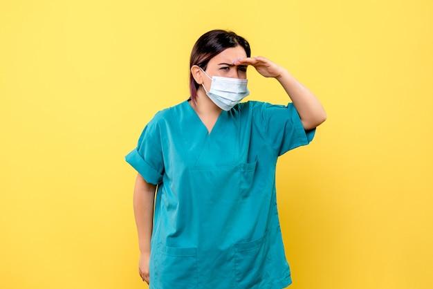 마스크를 쓴 의사의 측면에서 코로나 바이러스의 증상에 대해 생각하고 있습니다.