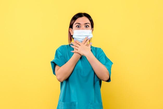 마스크를 쓴 의사의 측면은 그녀가 코로나 바이러스로 환자를 치료할 것이라는 것을 알고 있습니다.