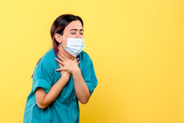 마스크를 쓴 의사의 측면이 코 비드의 증상에 대해 이야기합니다.