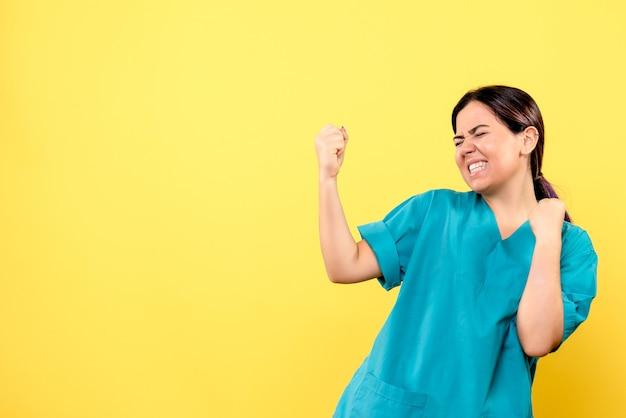 제복을 입은 의사 미소 짓는 의사의 측면보기는 코로나 바이러스에 걸린 환자를 도왔습니다.