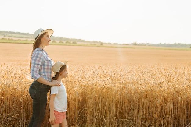 Вид сбоку на семью фермеров, женщину, мать и маленькую дочь в шляпах на головах возле ...