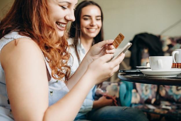 Вид сбоку на женские руки, использующие кредитную золотую карту и смартфон для онлайн-банкинга, сидя за столом в кафе с улыбающейся подругой.