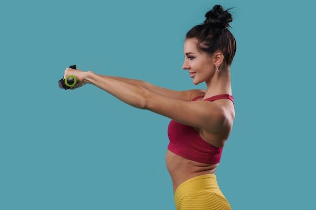 Вид сбоку на спортивную женщину, держащую гантели на вытянутых руках перед собой