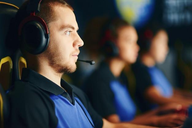 焦点を絞った白人男性、プロのチームでオンラインビデオゲームをプレイするヘッドフォンを着用し、ゲームクラブに座ってeスポーツトーナメントに参加している男性のサイバースポーツゲーマーの側面図
