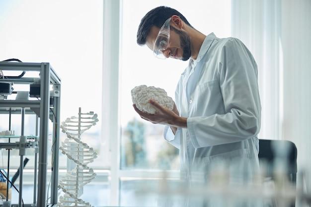 3d 인쇄 된 뇌 모델을 들고 집중된 검은 머리 수염 된 의대생의 측면보기