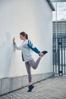 彼女の左足を後ろに曲げる焦点を絞った黒髪の若い運動白人女性の側面図