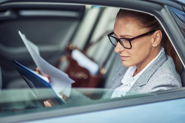 차에 뒷좌석에 앉아있는 동안 문서를 분석하는 안경을 쓰고 집중된 중간 나이 든된 비즈니스 여자의 측면보기. 운송 및 차량 개념, 사업 사람들