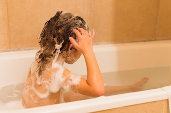 Side view of a girl bathing in tub
