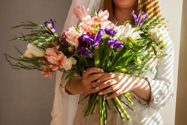 Вид сбоку девушки, держащей букет различных весенних цветов темно-фиолетовых ирисов с альстромерией, розовыми цветными тюльпанами, турецкой гвоздикой и пурпурным цветом статицы за светлым столом