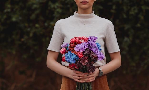 Вид сбоку девушки, держащей многоцветный букет цветов гвоздики на темной стене
